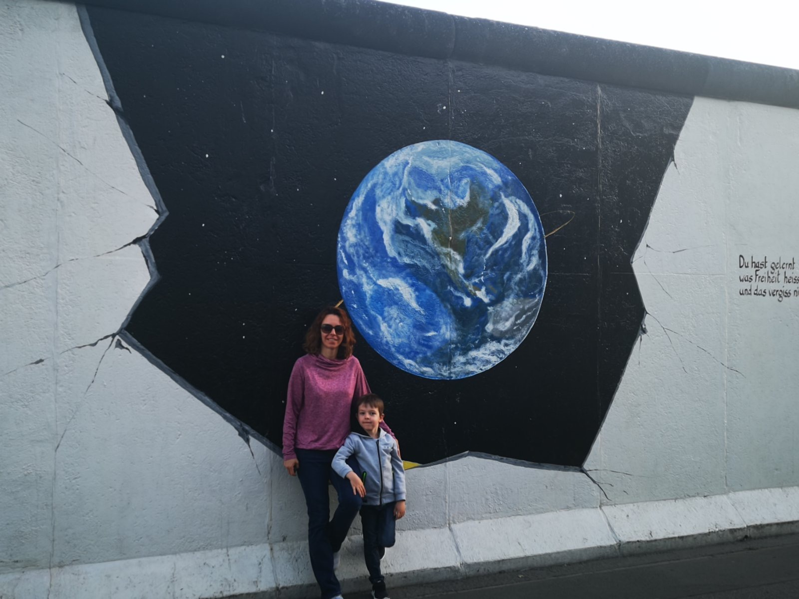 Nadja and son in front of street art.