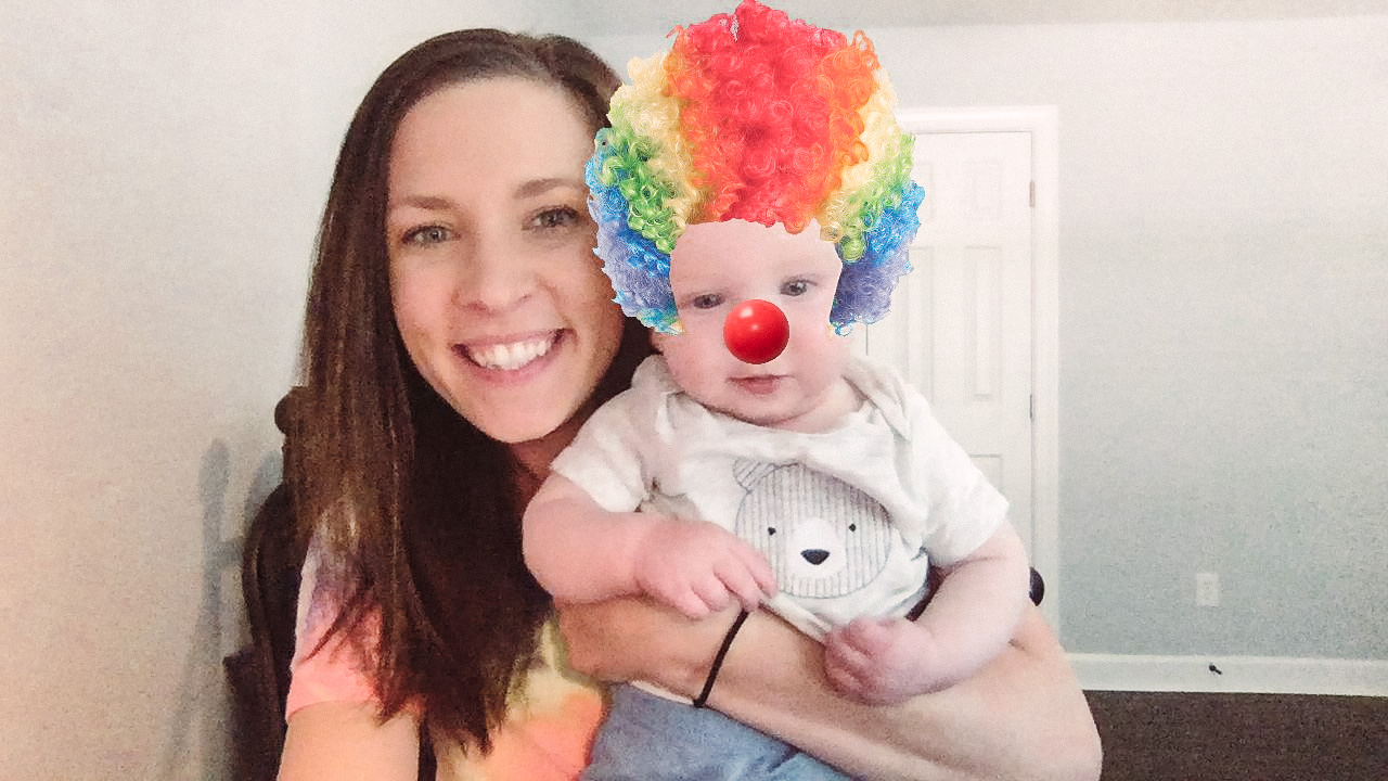 Jen and her son pose for a photo. Her son has a clown face filter on.