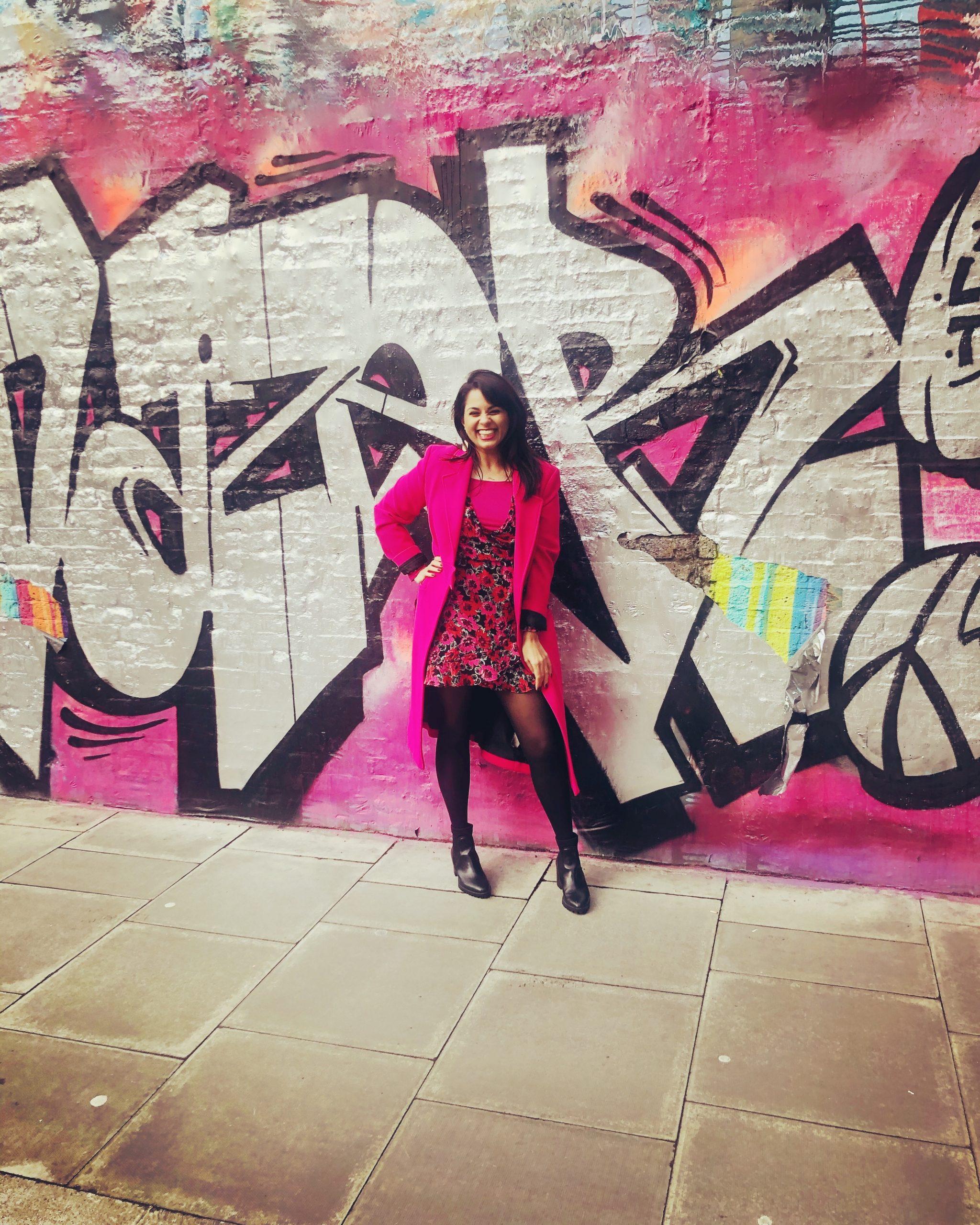 Alpa standing in front of grafitti.
