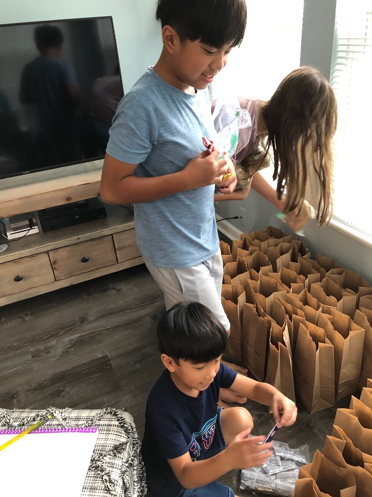 Maria's family helps to package meals.
