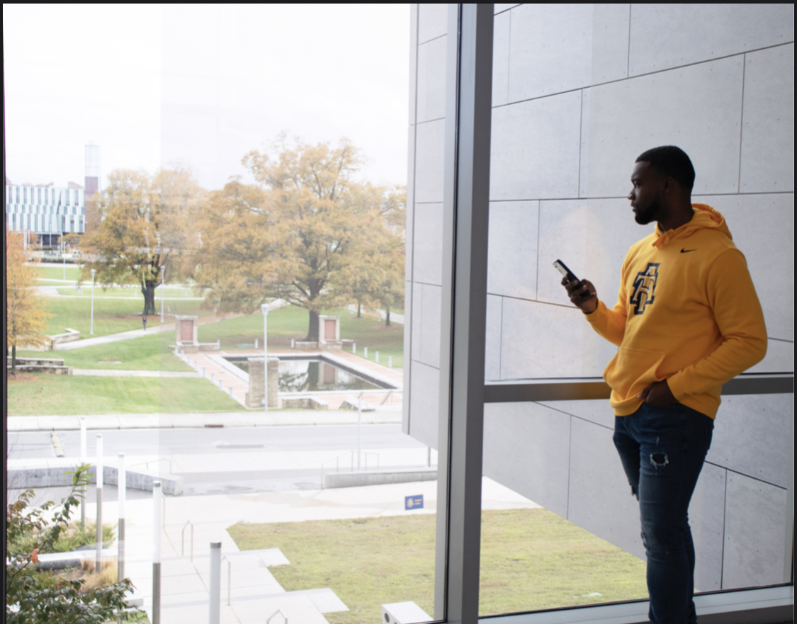 Michael holds his phone and looks out the window.