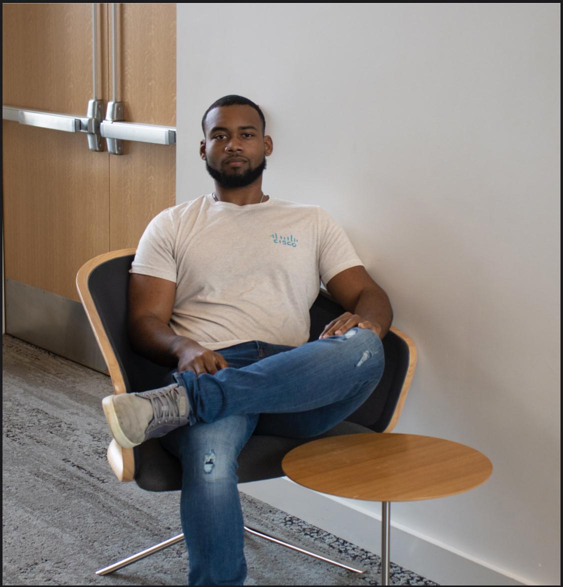 Michael sitting in chair wearing Cisco shirt.