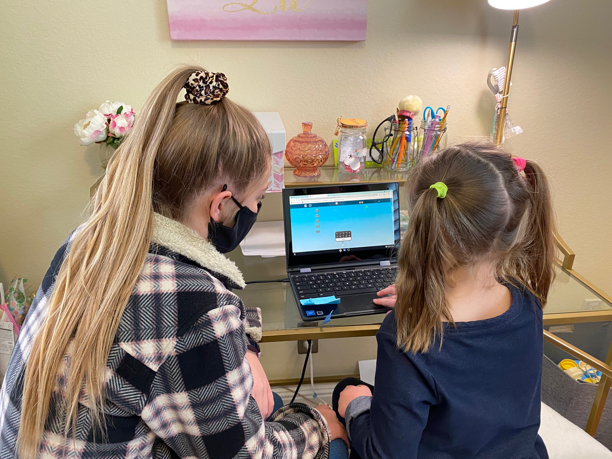A child and adult work at computer.