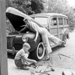 """ord Super Deluxe """"Woodie"""" station wagon, first introduced late 1940. Women & boy making repairs"""