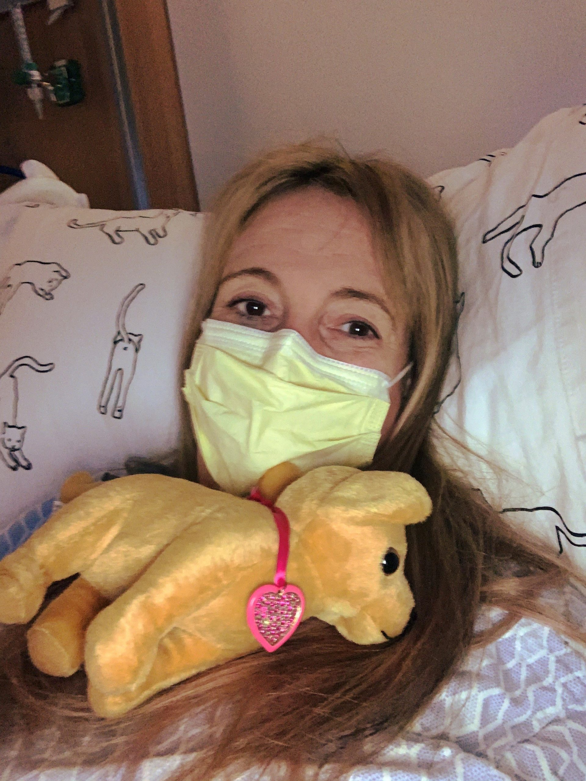 Rachael wearing mask with a stuffed animal while laying in hospital bed