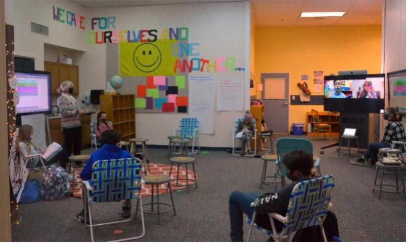 hybrid classroom with students sitting in fold out chairs and teacher instructing using Webex