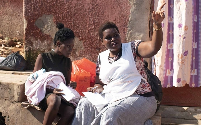 A mother and her infant with a community health worker