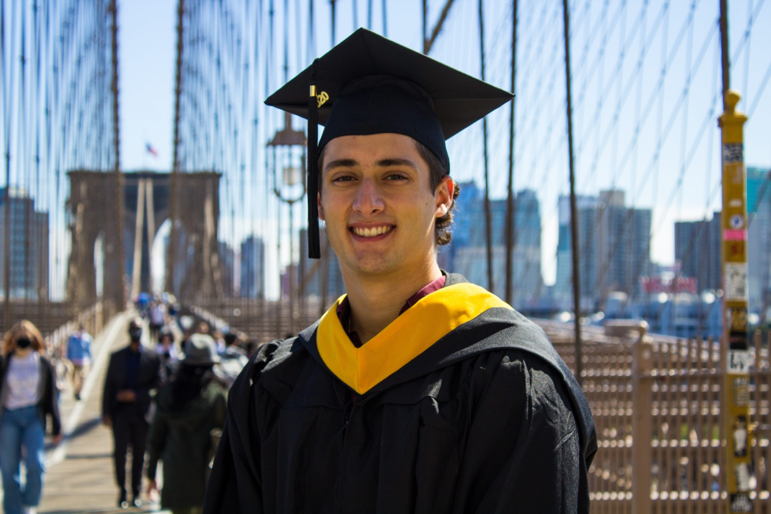 Nic standing on a bridge in cap and gown