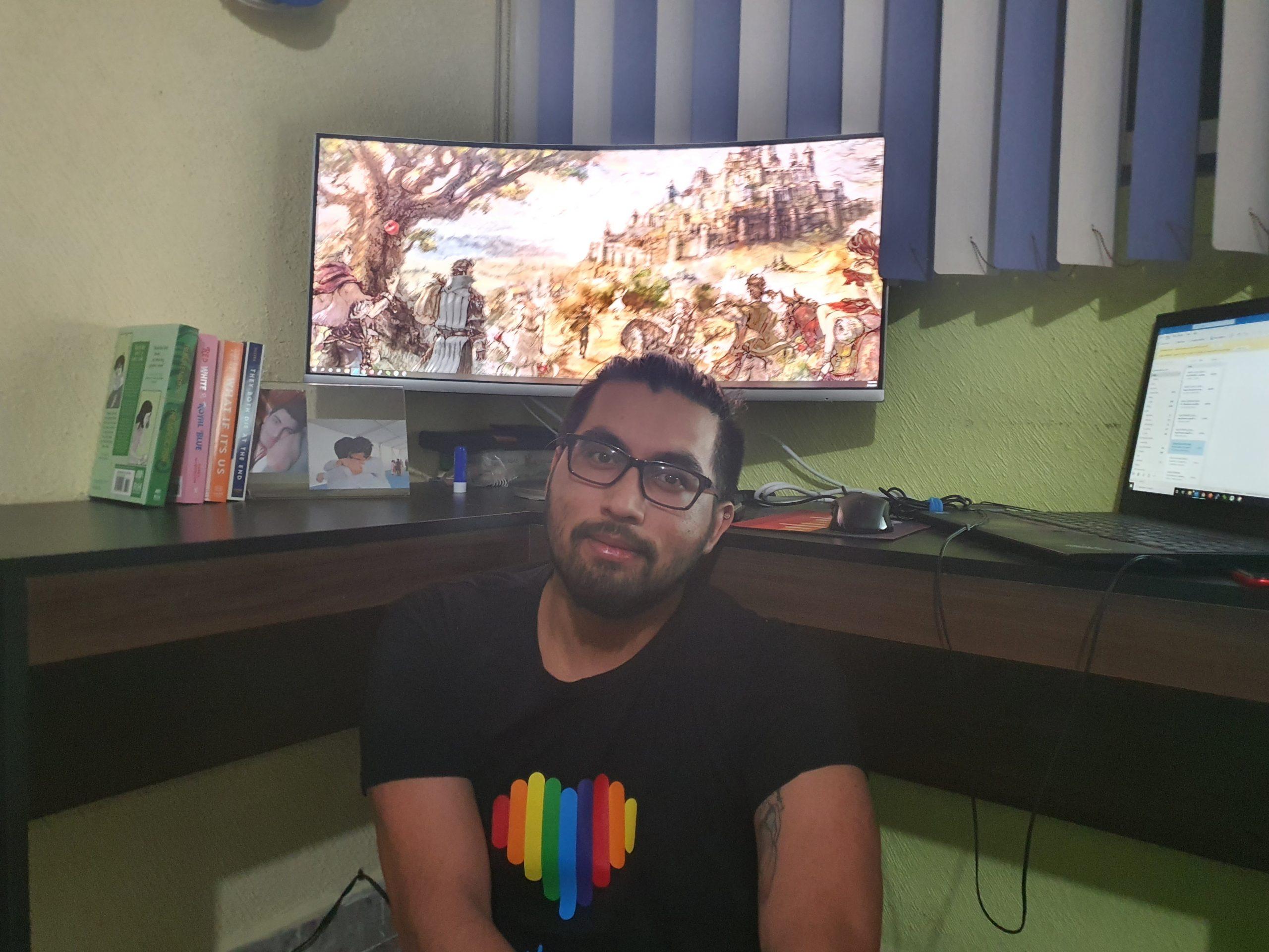 Jesus sitting in front of computer in pride shirt