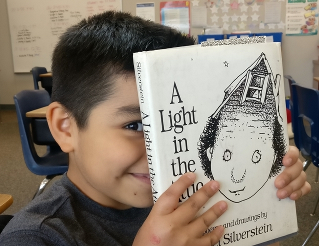 A boy holding a book up to his face