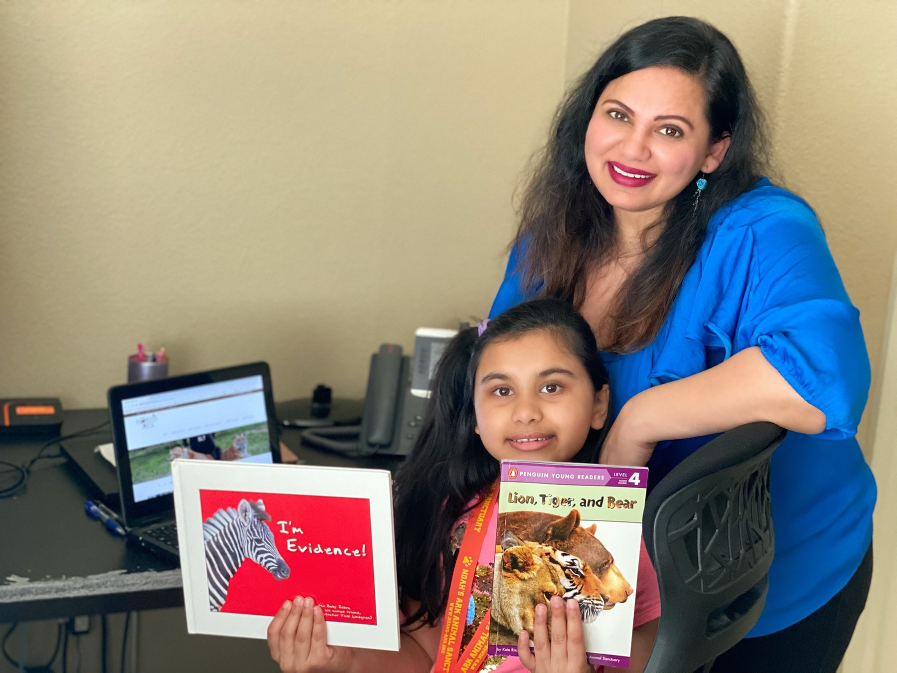 Karishma stadning behind her daughter, while she holds up books that she's read