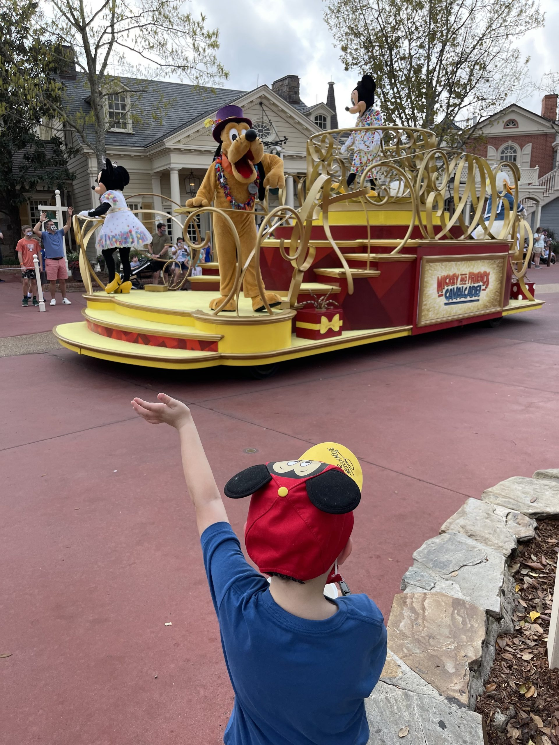 Tommy's son waves to Pluto during parade.