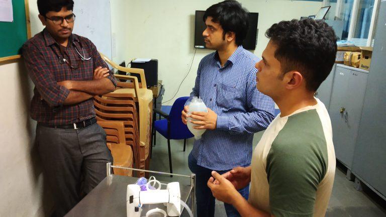 Three men talking in front of a ventilator