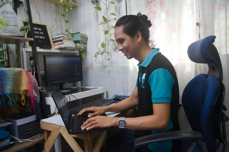 Ryan is wearing a teal and black polo shirt with Virtualahan logo. He is smiling while working on his laptop. He is in his workstation with an extra monitor, books, trophies, and hanging plants.