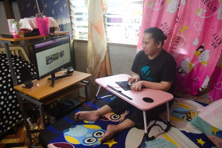 Grace is sitting in her bed while looking at her computer monitor and holding the mouse. She is wearing a black shirt with Virtualahan logo on it. She is in her room with a pink hello kitty curtain.