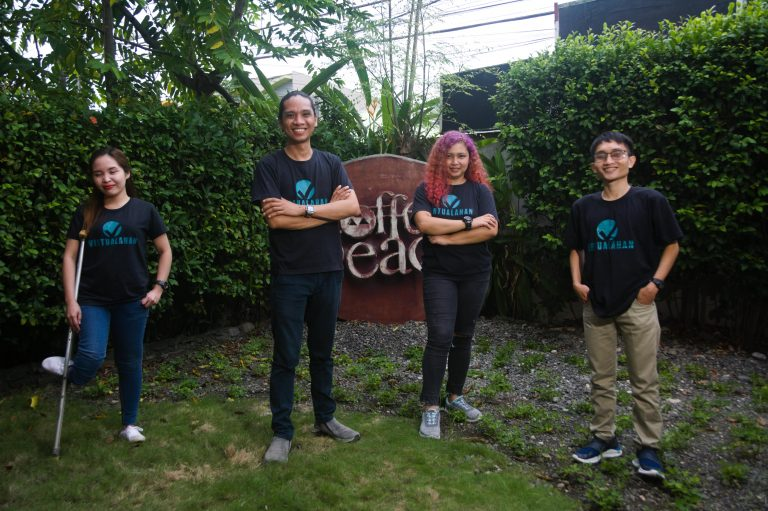 Four millennials (two females and two males) wearing black with Virtualahan logo on it striking a pose with green plants in the background.