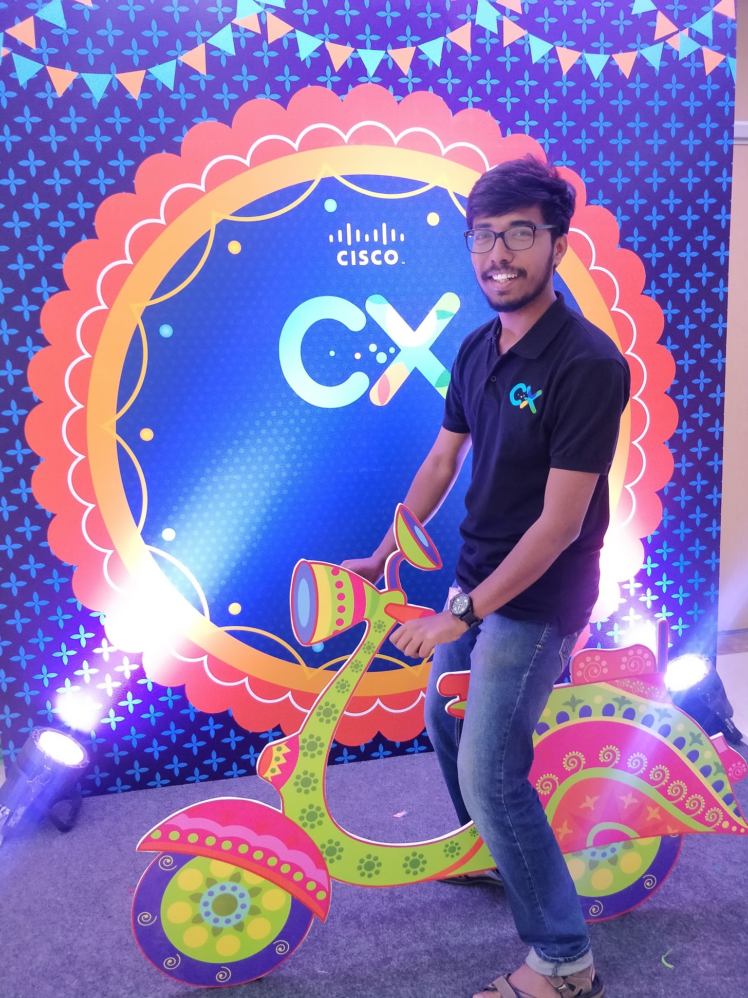 Vivek in front of a CX poster.