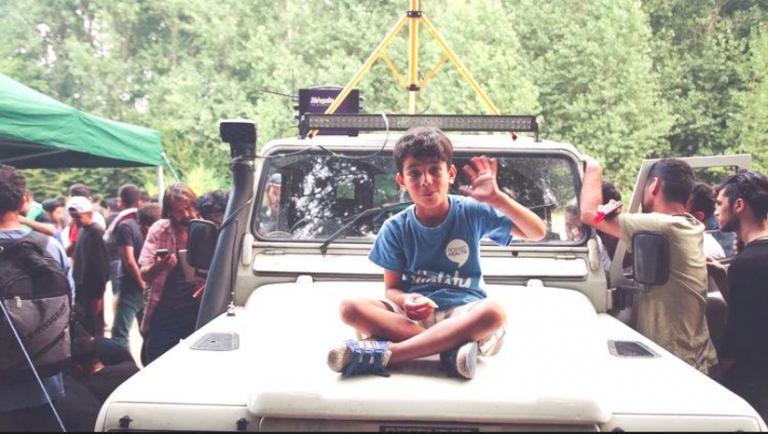 Boy sitting on hood of car