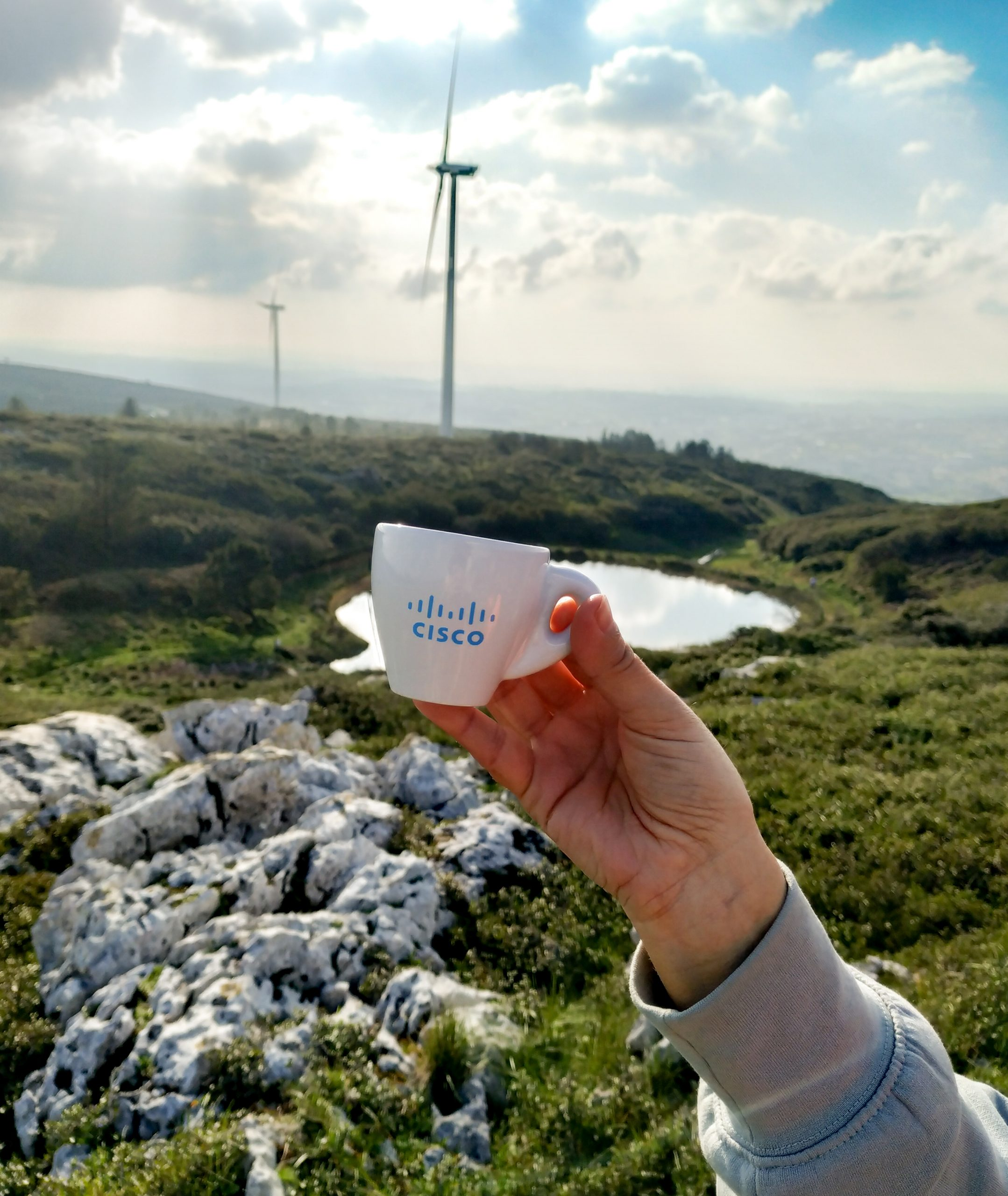 Holding up espresso cup overlooking grassy hills and rocks.