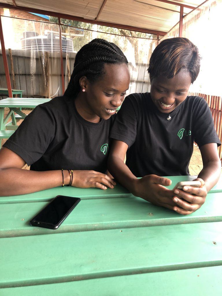 Two young women sitting side by side looking at a smartphone