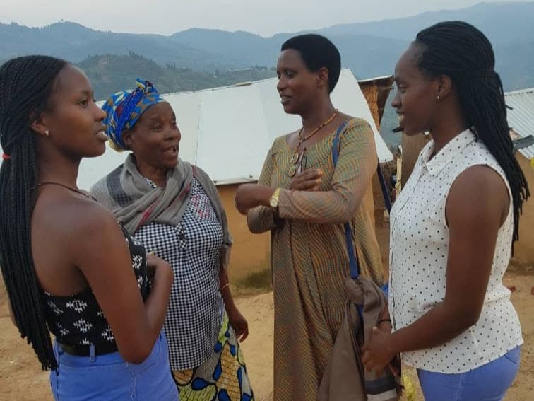 A group of four women standing and talking to one another