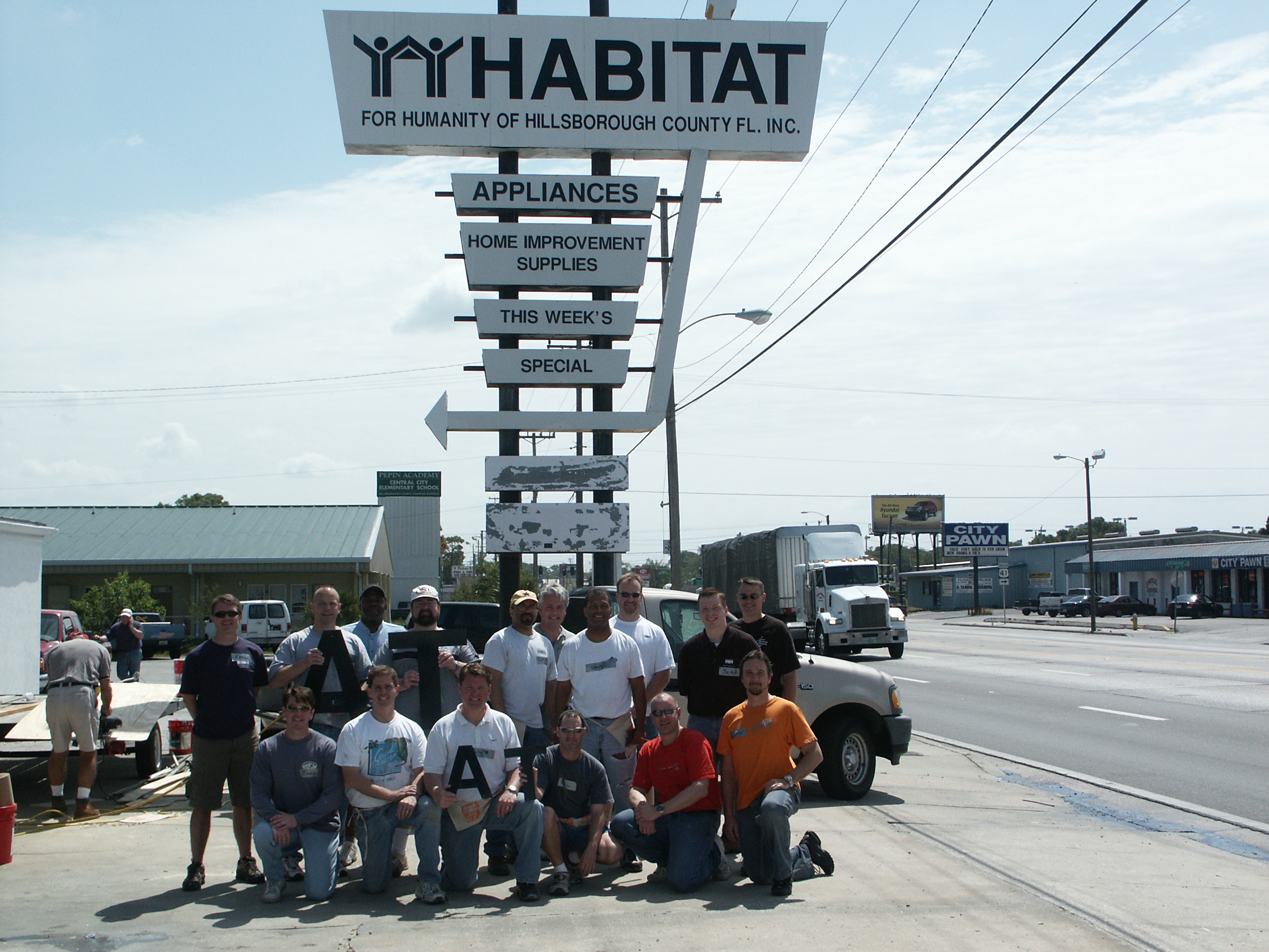 Team photo in front of Habitat for Humanity sign.