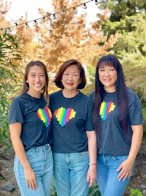 Renee, her daughter and her mother stand, smiling, while wearing Cisco Pride Heart tshirts.