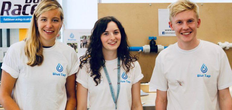 Three young people wearing matching shirts