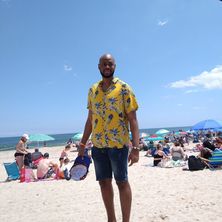 A young man wearing a bright shirt on a beach