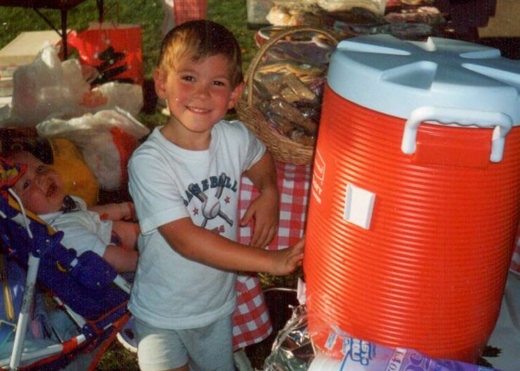 A young boy standing next to a water cooler