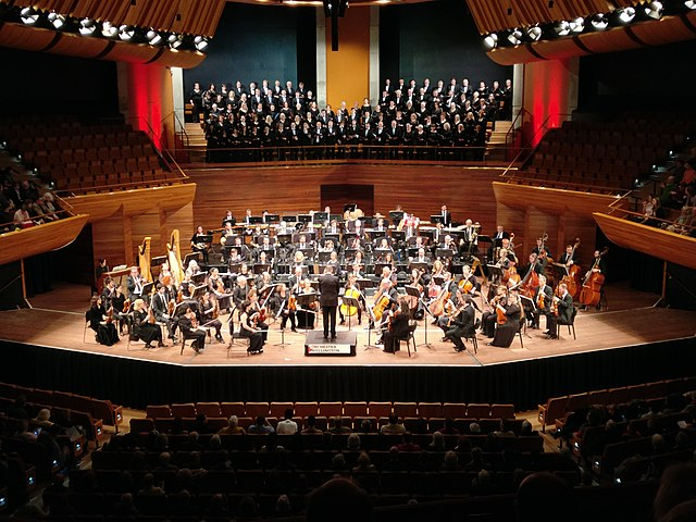Orchestra Wellington in concert in August 2017 with conductor Marc Taddei, at the Michael Fowler Centre in Wellington, New Zealand. Jonathan Harker https://commons.wikimedia.org/wiki/File:Orchestra_Wellington_in_concert_at_the_MFC.jpg