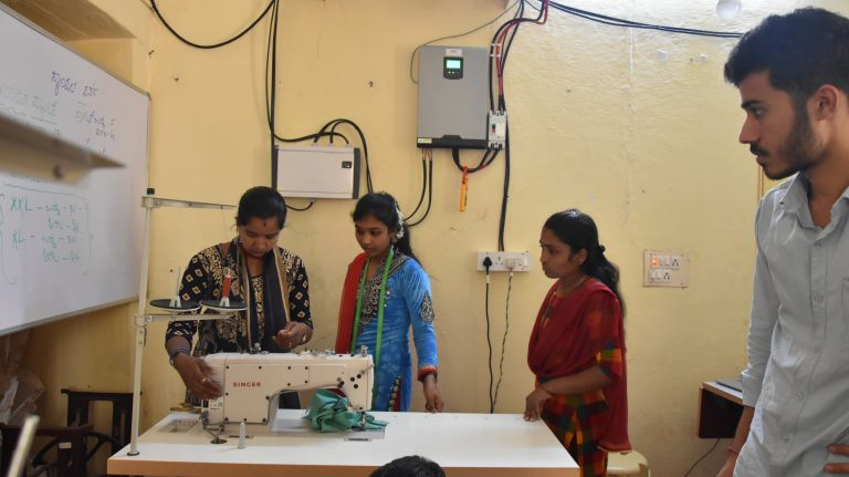 Three women standing in front of a sewing machine with a man standing off to the side