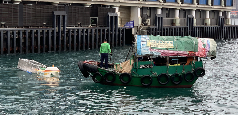 A robot picking up trash in the ocean next to a boat