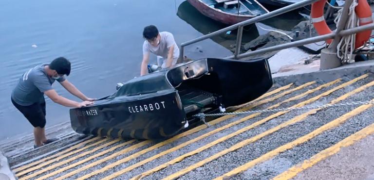 Two men launching a mini-boat