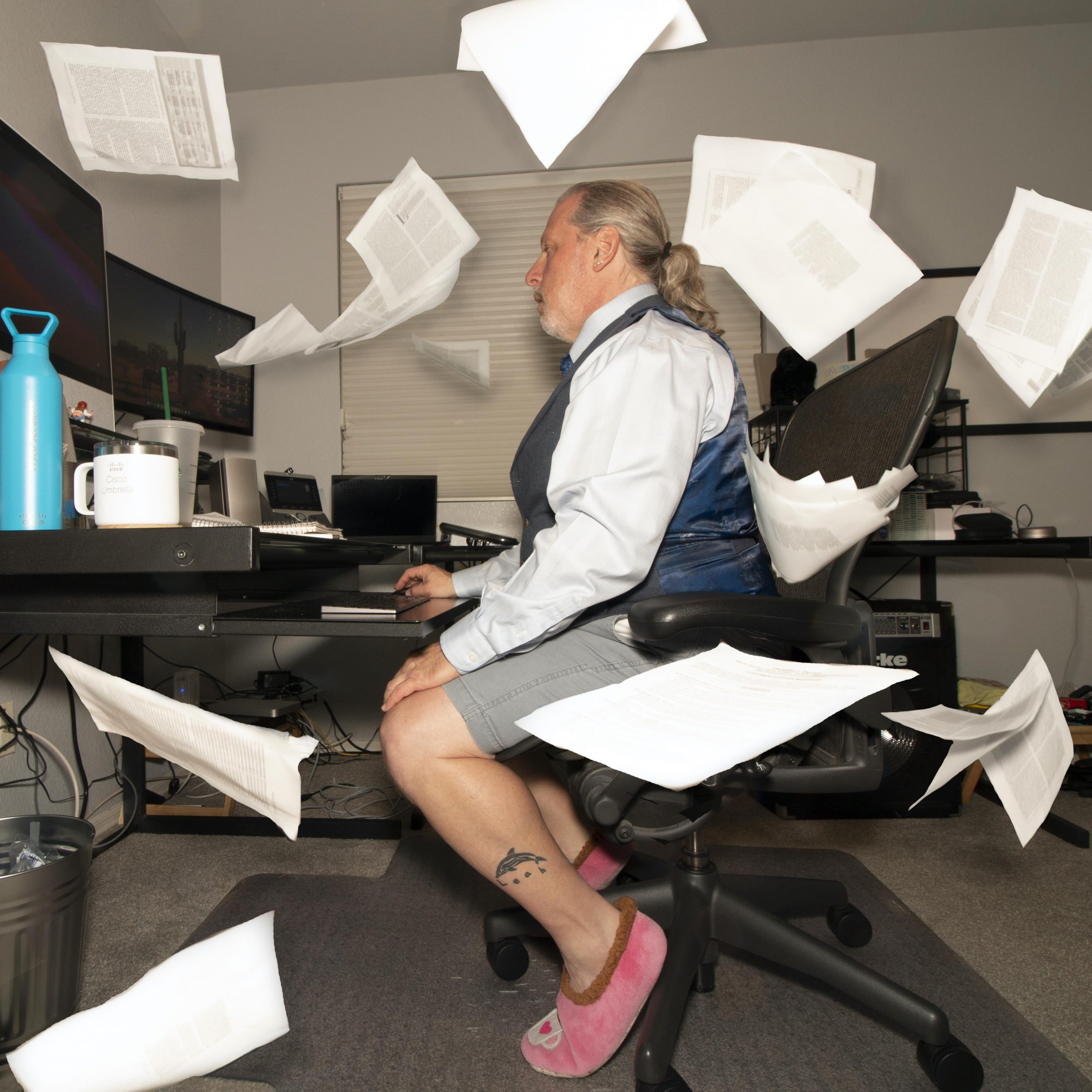 Ken sits at his desk as papers fall all around him.