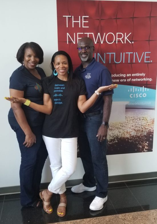 Shawnita, her husband Vanis, and her Mom Lovey all smile in their Cisco shirts in front of a Cisco advertisement.