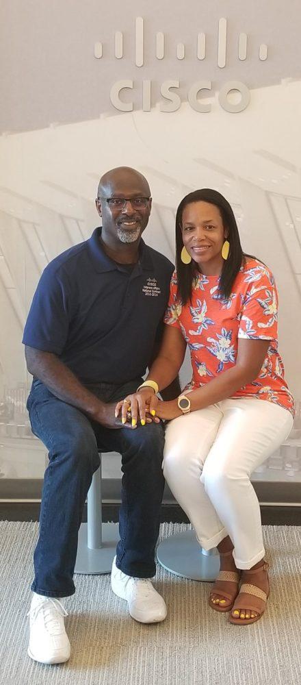 Shawnita and her husband Vanis smile under a Cisco logo.