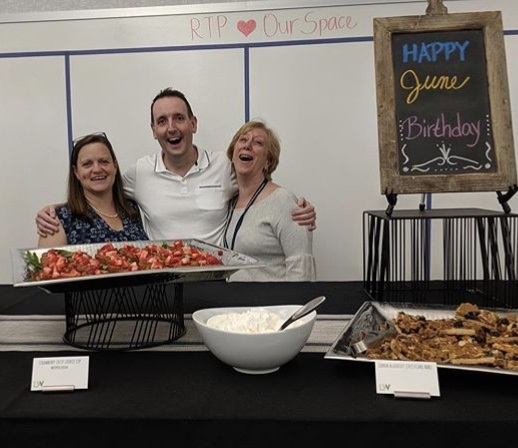 Jeff and two of his peers standing with food and signage for the Workplace Resources monthly birthday party.