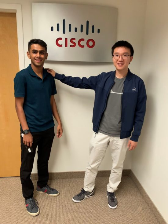 Dhwan standing with a colleague in front of a Cisco office sign.