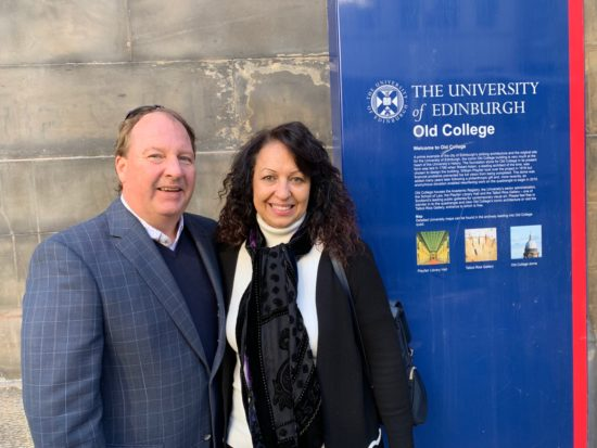 Ed smiling next to a sign that reads The University of Edinburgh Old College.