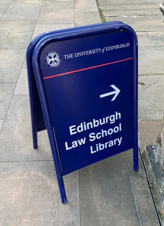 A dark blue sign pointing towards the Edinburg Law School Library