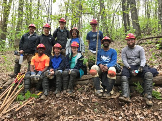 Emilio and his fellow interns wearing hard hats in the woods at a give back event.