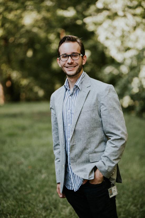 Emilio smiling in his glasses, a sport coat, and Cisco badge.