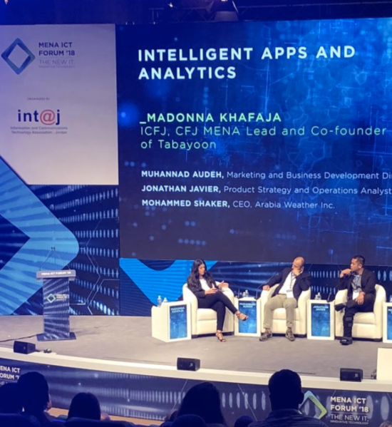 Jonathan sitting on stage with two other speakers giving a talk on Intelligent Apps and Analytics.