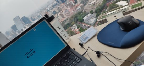 Yartiza's Cisco badge and laptop with a Cisco background on a desk overlooking Mexico City.