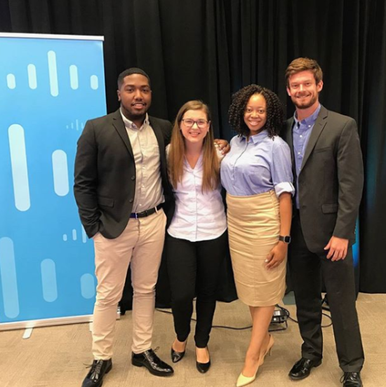 Chloe smiles with colleagues in front of a Cisco backdrop.