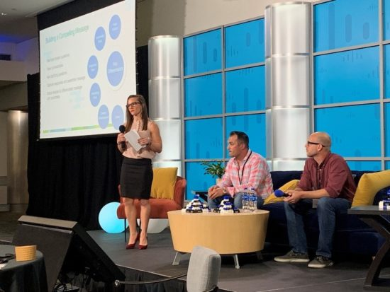Jeane presenting on stage at Cisco next to two of her peers.