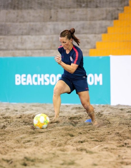 Jeane running after a soccer ball on a beach in her uniform.