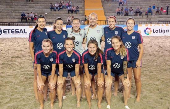 Jeane smiles with her teammates, the U.S. Women's Beach Soccer National Team.