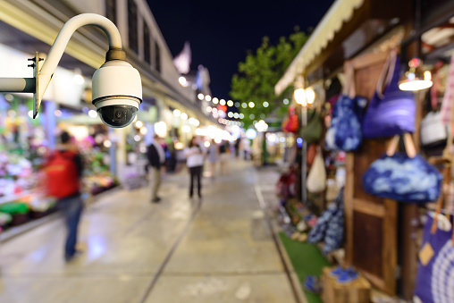 Security camera monitoring events in shopping center at night.